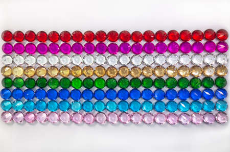Colorful diamonds are arranged neatly in a row on a white floor.