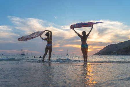 Two woman poses with a beautiful sarong on the beach during the outbreak not many tourists on Nai Harn beach. but still have local people on the Nai Harn beach Phuket Thailand.