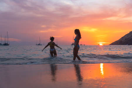 Two women playing on the beach in the beautiful sky. Stock Photo