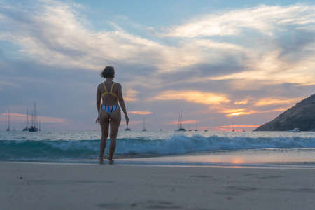lady walking on the beach in sunset Stock Photo