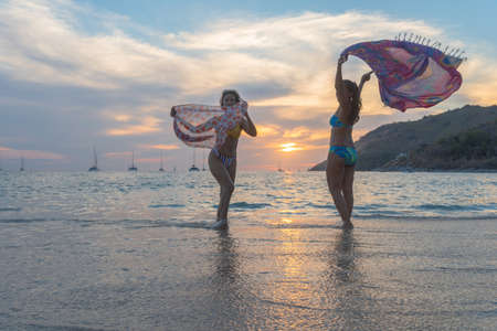 Two woman poses with a beautiful sarong on the beach Zdjęcie Seryjne