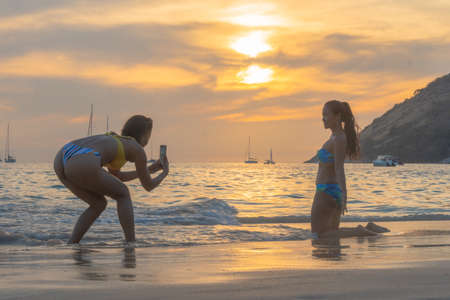two ladies taking pictures on the beach.