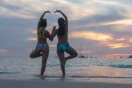 Two women posing beautiful on the beach.