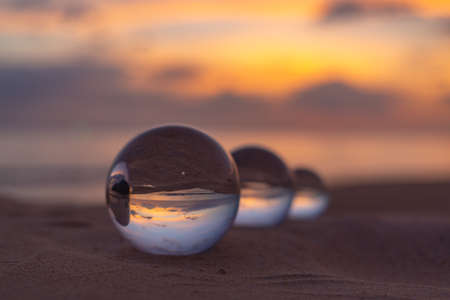 Three clear crystal balls of three sizes are sphere reveals seascape view with spherical placed on the sand at Karon Beach during sunset. Stockfoto