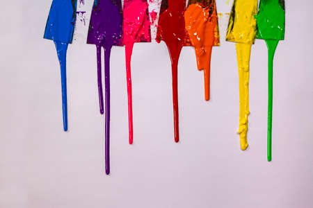 blue ,purple, pink, red,orange, yellow and green are slowly dripping from color scoop handle.and slowly spread onto the white paper.
