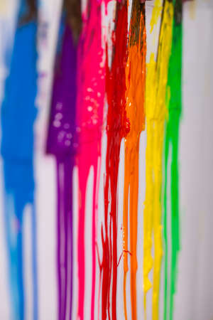 blue ,purple, pink, red,orange, yellow and green are slowly dripping from color scoop handle.