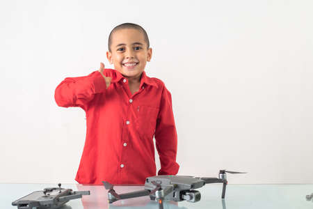 Cute boy with skinhead hairstyle in a red long-sleeve shirt is assembling a drone on a clear glass table with a white backdrop Stock Photo