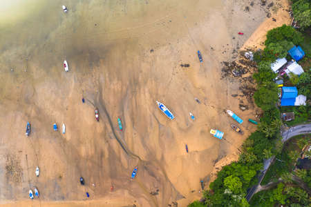 aerial top view fishing boats parking on the beach during low tide at Rawai beach Phuket Thailand.sea without water in low tide fishing boats stuck in the mud.sand beach background.