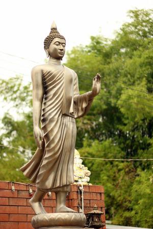 Buddha statue stands on a pedestal.