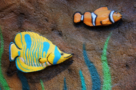 Small fish statue on a stone wall.