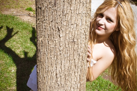 Young girl playing hide behind a tree