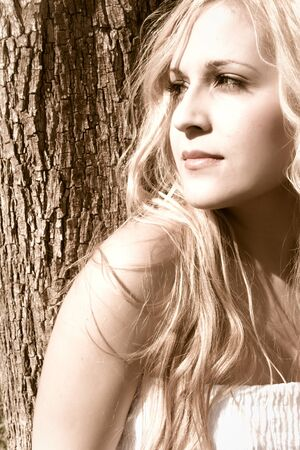 chica: Beautiful young girl against a tree waiting for someone  Stock Photo