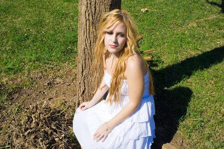 pretty young woman in a white dress in the field