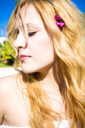 portrait of beautiful woman with a flower in her blond hair hanging