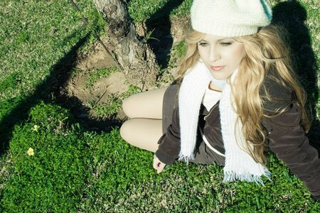 Beautiful young girl sitting on the grass