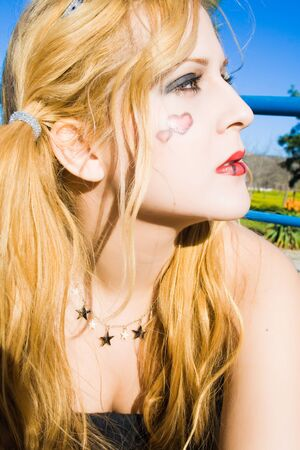 portrait of beautiful young woman with a heart painted Gothic in the face  Stock Photo