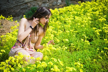 beautiful young hippie sitting among the flowers and smelling one of them