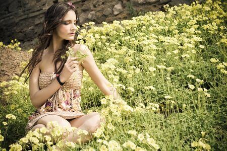 hippie young girl sitting in a field full of yellow flowers