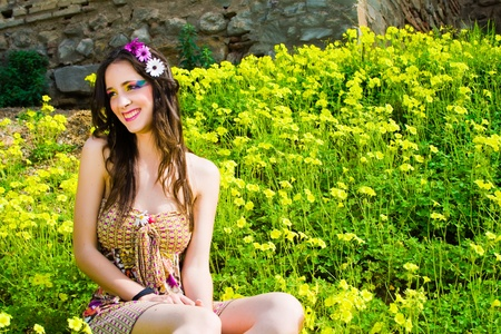 Hippie girl and happy sitting in a field of flowers smiling