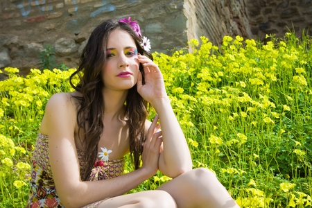 beautiful hippie girl sitting in a flower field facing the camera  Stock Photo