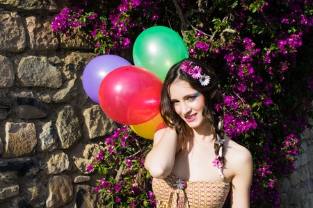hippie girl with colorful balloons posing for the camera