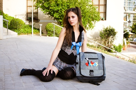 Young schoolgirl on the floor with her backpack  Stock Photo