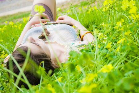 Young hippie girl lying in the field of yellow flowers  Stock Photo