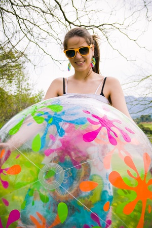 beautiful hippie girl with colored ball teaching the camera