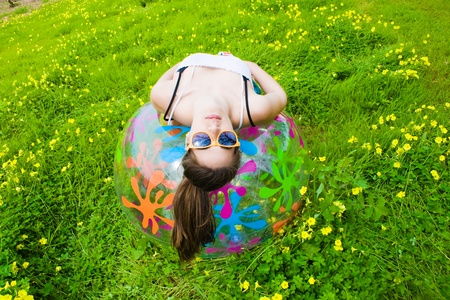young hippie girl lying on her colored ball and facing the camera with his sunglasses  Stock Photo