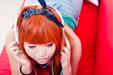 Japanese girl listening to music with headphones