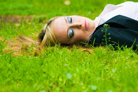 business woman lying in grass