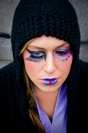 Young girl with colorful makeup and black hood