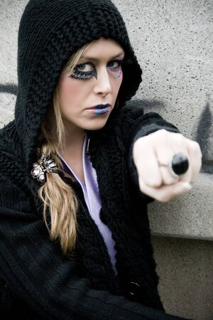 young blonde girl with dark hood showing the ring Stock Photo