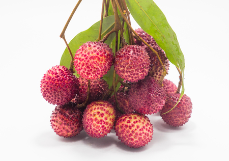 Lychee. Fresh lychees peeled showing the red skin and white flesh with green leaf on white background.