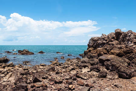Yello rock and sea with blue sky. Stock Photo