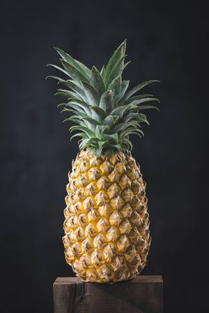 Fresh pineapple on the dark background
