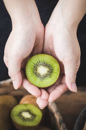 Fresh kiwi  slices in woman hand on the dark background