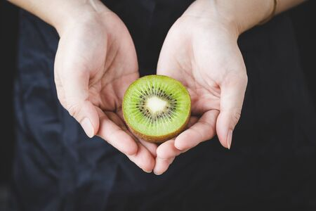Fresh kiwi slice in woman hand on the dark background Banco de Imagens
