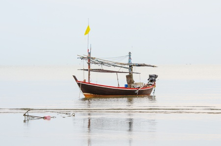 The Boat with the Anchor on the beach at Krabi province, Thaniland  This one is the boat of poor fisherman because it very small for fishery for live  photo