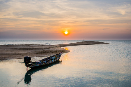 Traditional Long-Tailed Boat is cast anchor on the beach with sunset. photo