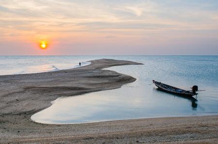 Bateau en bois est jeta l'ancre sur la plage avec le coucher du soleil.