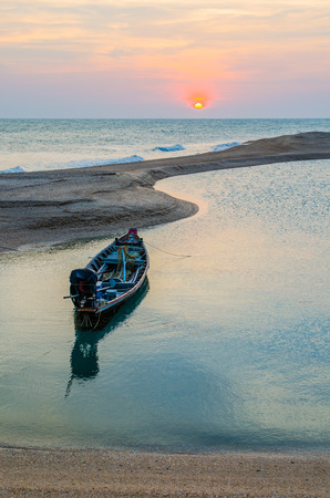 Traditional Long-Tailed Boat is cast anchor on the beach with sunset photo