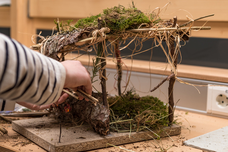 Child is making a crib on branches and moss for Christmas