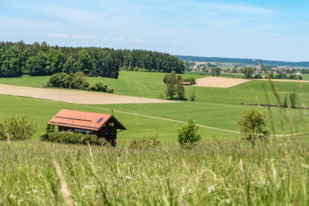 Beautiful idyllic landscape with hut in front of blue sky in Germany Bavaria