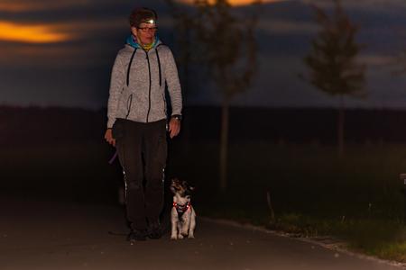 Vrouw gaat 's nachts met een hond wandelen in de herfst met zaklamp - jack russell terrier doggy