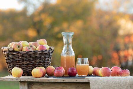 Świeży sok jabłkowy z jabłek jesienią po zbiorach, podawany na stole o zachodzie słońca