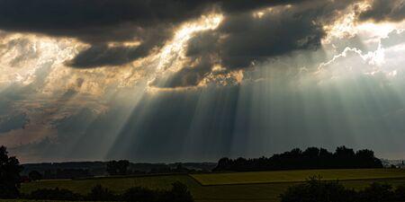 rayons de soleil dans le ciel avec des nuages d'orage noirs dramatiques Banque d'images
