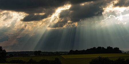 sunrays in the sky with dramatic black thunderclouds