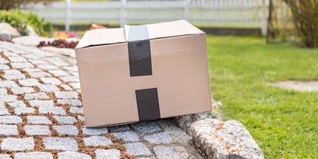 Parcel from postal delivery is left in the garden because the recipient is not at home.