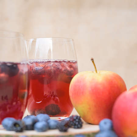 Red berries Cocktail with blueberries in front of a blurred brown background